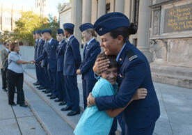 Cadet Carissa Silva of the University of New Haven hugs her little brother at the ROTC Oath of Enlistment ceremony.